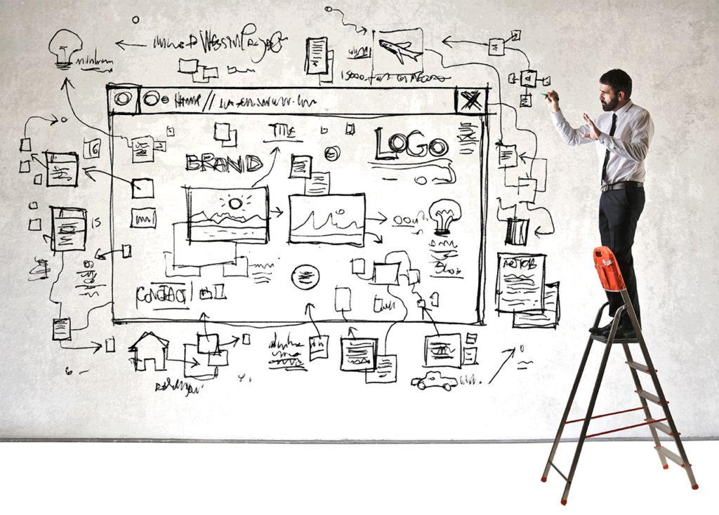 Mann vor grosser Wandtafel erklärt die Funktion von Webdesign